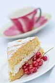 Ein Stück Victoria Sponge Cake mit roten Johannisbeeren