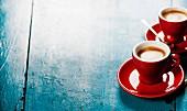 Zwei rote Espressotassehn auf blauem Holzuntergrund