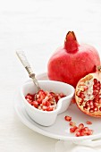 Pomegranate Seeds, some peeled and whole on a white background