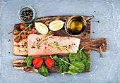 Zutaten für gesundes Abendessen: Lachsfilet, Spinat, Tomaten und Chilischote