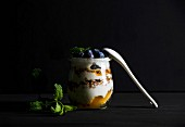 Yogurt and oat granola with jam, blueberries and mint leaves in glass jar on black background