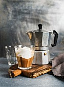 A glass of coffee with ice cream and steel moka pot on on rustic wooden board