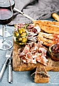Meat appetizer selection: Salami, prosciutto, bread sticks, baguette, olives and sun-dried tomatoes