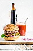 Fresh homemade burger on wooden serving board with spicy tomato sauce and bottle of dark beer