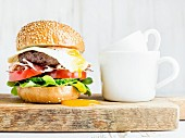 Breakfast set: Homemade beef burger with fried egg and vegetables and coffee cups on wooden board