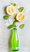 Green lemonade bottle with ingredients: lemons, mint and ice cubes