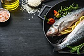 Raw uncooked seabass fish with herbs, spices and rice in cast iron cooking pan on black wooden background
