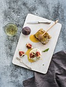 Camembert cheese with fresh figs, honeycomb and glass of white wine on serving board