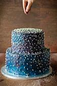 Zweistöckige blaue Torte mit Silberperlen