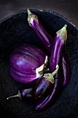 Different eggplants in a rustic bowl