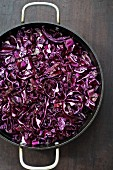 Shredded red cabbage in a pan on wooden table