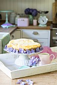 Cheesecake decorated with hydrangeas on a wooden tray
