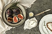 A still life with figs, goat's cheese, thyme, honey and Bauernbrot (German farmhouse bread)