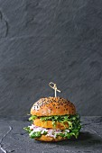 Homemade veggie sweet potato burger with fresh radish and pea sprouts served over black textured background