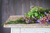 Frische Kräuter: Minze, Oregano, Thymian und blühender Salbei auf Holztisch