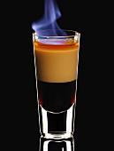 Flambierter B52 im Glas vor schwarzem Hintergrund