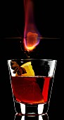 A burning sugar cube over a glass of Feuerzangenbowle