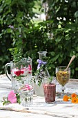 Various herbal drinks on a garden table