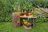 Verschiedene selbstgemachte Ölsorten auf Holztisch im Bauerngarten