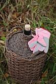 Korbflasche und Gartenhandschuhe auf der Wiese