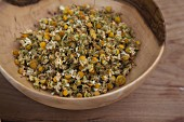 Dried camomile flowers in a wooden bowl