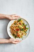 Hände präsentieren vegetarischen Couscoussalat