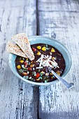 Black bean soup topped with roasted peppers and cilanrto on a rustic white wooden background