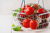 Assortment of cherry tomatoes with garlic and basil in small market food basket over white wooden surface