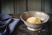 Shortcrust pastry dough in vintage metal bowl over old wooden table
