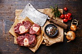 Raw fresh cross cut veal shank and seasonings for making Osso Buco on wooden background with meat cleaver