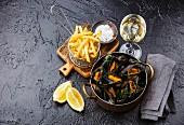 Miesmuscheln in Kupfertopf mit Weisswein und Pommes frites auf schwarzem Steinuntergrund