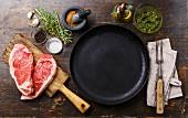 Rohe Striploin Steaks in Herzform, Gewürze und Kräuter um Bratpfanne
