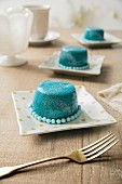 Petit four cakes with aqua mirror glaze, glitter and dragees