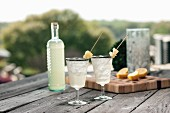 Bottled gin punch with pineapple garnish in silver rimmed glasses outdoor