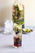 A glass with blueberry infused water and fresh mint