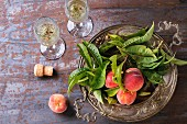 Peaches on branch with leaves in white vintage plate and two glass of champagne with cork over old metal background