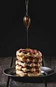 Metal plate with homemade belgian waffles with pouring syrup from tea spoon over old wooden table
