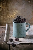 Spotted blue ceramic mug of dewberries, at old wooden table with tin