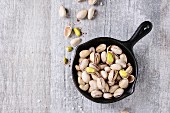 Salted roasted pistachios nuts with shell and salt in black small cast-iron pan