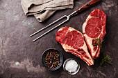 Zwei rohe Ribeye-Steaks, herzförmig arrangiert, mit Rosmarin, Pfeffer und Salz auf Schieferplatte