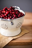 Bright red cranberries in a cream colored strainer