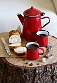 Coffee in red enamel cups and a jug served with a Swiss roll cake on a tree trunk
