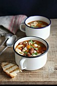 Two enamel mugs of minestrone soup with pasta, beans and vegetables