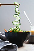 Chopsticks holding spiral cucumber over a salad