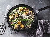 Vegan runner bean dish with mango and curry tofu and bean sprouts, served in a pan