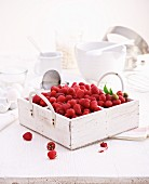 A still life with fresh raspberries in a wooden crate, and pastry utensils in the background