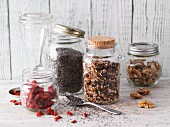 Storage jars of chia seeds, muesli, goji berries and walnuts