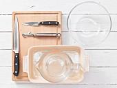 Verschiedene Küchenutensilien: Glasschale, Messbecher, Auflaufform, Messer, Sparschäler