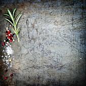 Pfefferkörner, Rosmarin und Salz auf rustikalem Untergrund