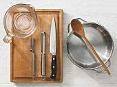 Kitchen utensils: measuring cups, vegetable peeler, knives, pot, wooden spoon